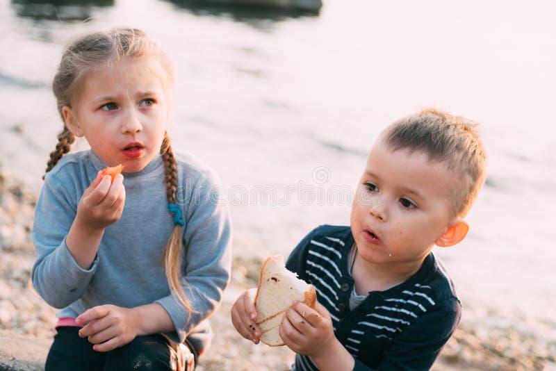 I bambini del mare mangiano il pane della ragazza e del ragazzo del pomodoro tostato immagine stock