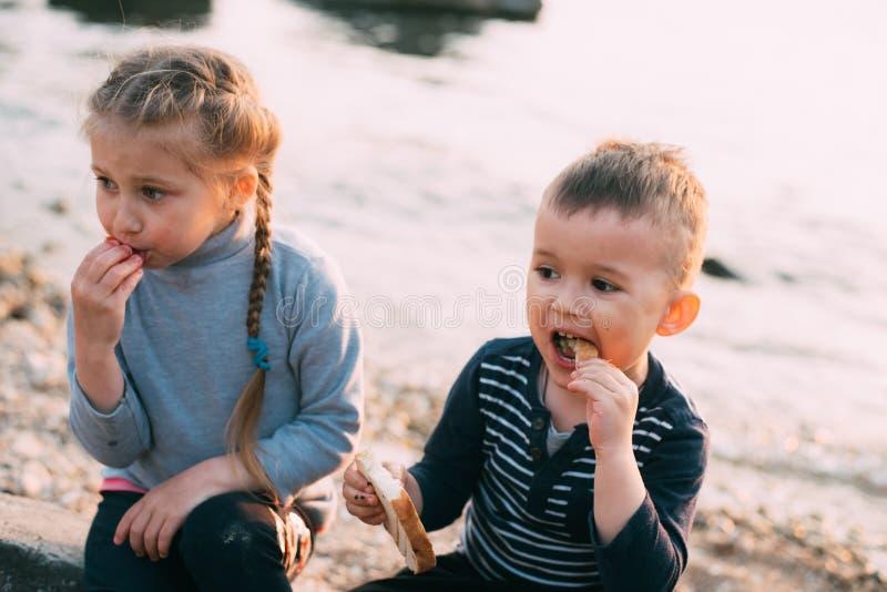 I bambini del mare mangiano il pane della ragazza e del ragazzo del pomodoro tostato immagini stock