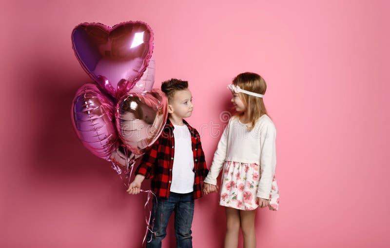 I bambini della ragazza e del ragazzino con i palloni di colore pastello per il giorno o il compleanno di biglietti di S. Valenti fotografia stock libera da diritti