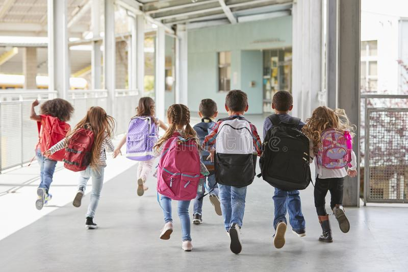I bambini della scuola elementare si allontanano dalla macchina fotografica in corridoio, fine su immagini stock libere da diritti