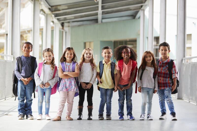 I bambini della scuola elementare stanno in corridoio che esamina la macchina fotografica fotografia stock