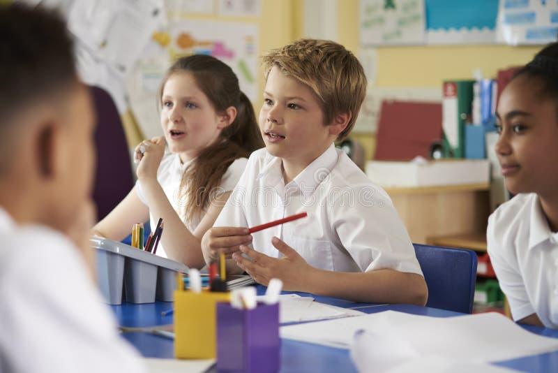 I bambini della scuola primaria lavorano insieme nella classe, fine su fotografia stock