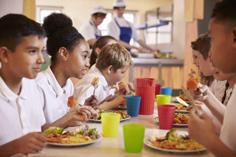 I bambini della scuola primaria mangiano il pranzo nel self-service di scuola, fine su fotografie stock libere da diritti