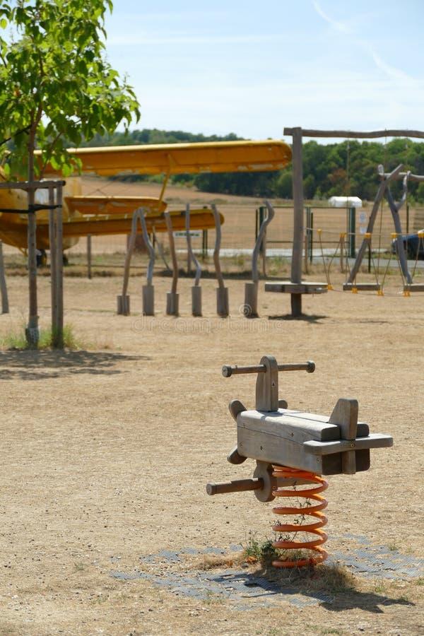 I bambini di legno oscillano in un campo da giuoco all'aeroporto fotografia stock libera da diritti