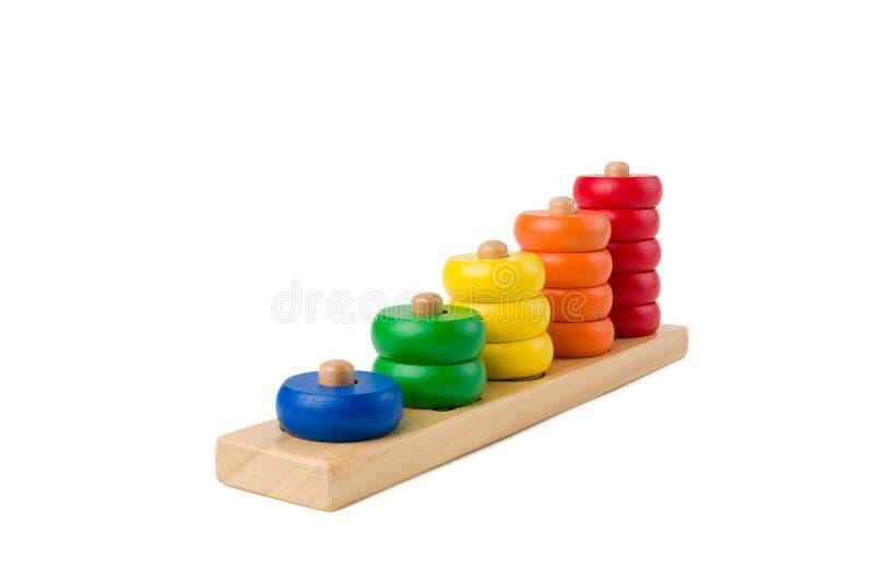 I bambini di legno variopinti giocano i punteggi da uno a cinque figure degli anelli colorati isolati su un fondo bianco Impilame fotografia stock