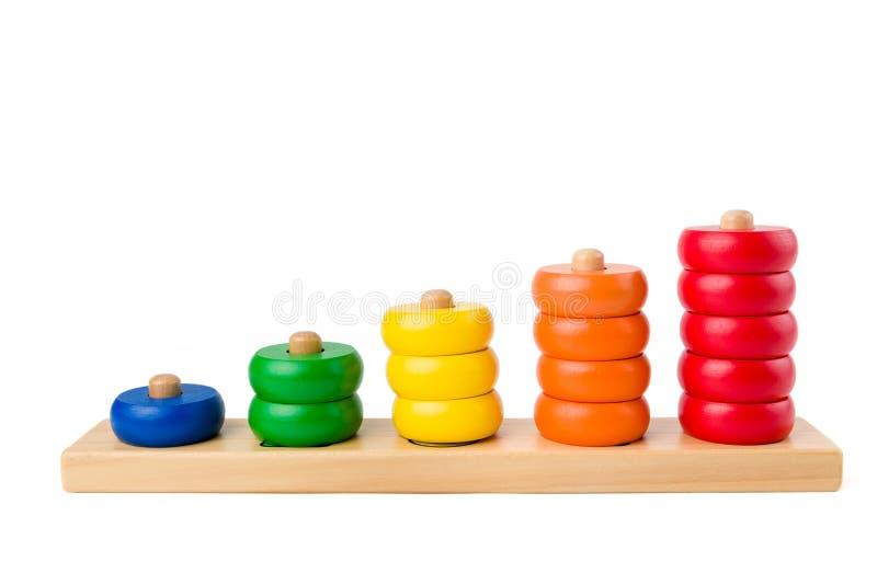 I bambini di legno variopinti giocano i punteggi da uno a cinque figure degli anelli colorati isolati su un fondo bianco Colpo de fotografia stock