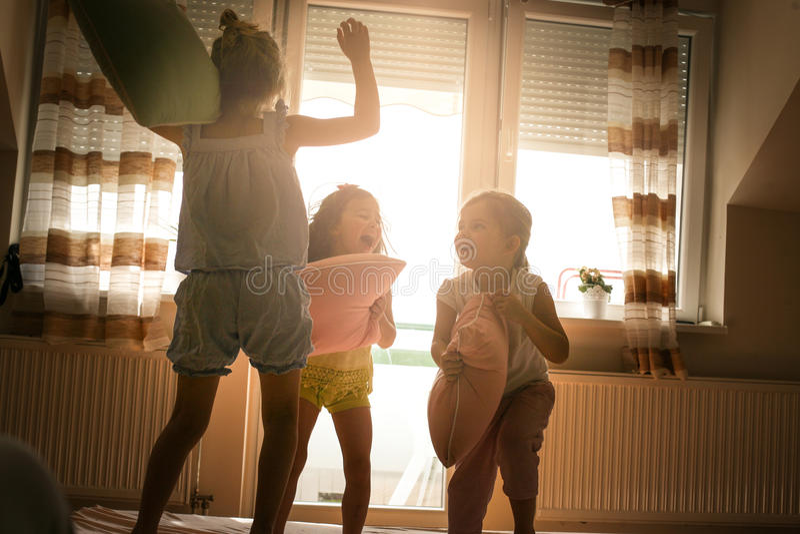 I bambini divertendosi sul letto e litigano con i cuscini fotografia stock