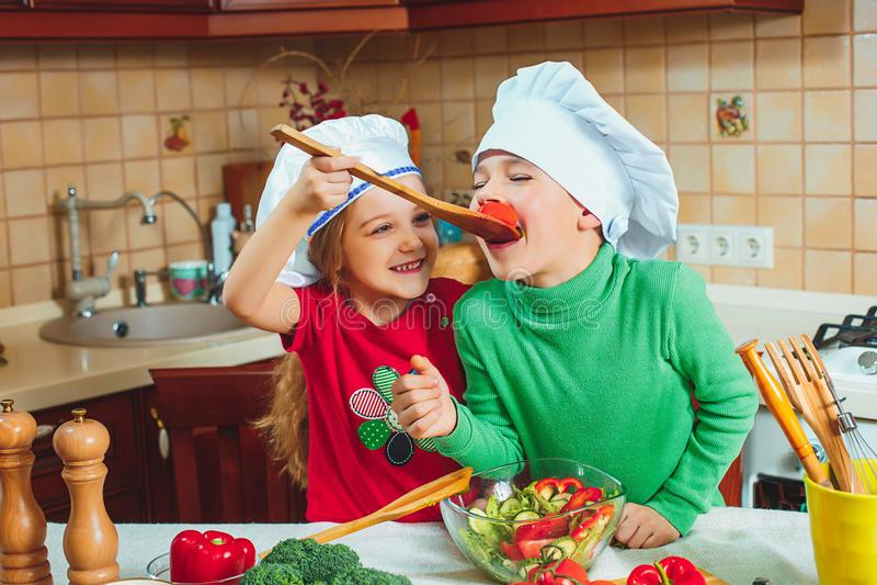 I bambini divertenti della famiglia felice stanno preparando un'insalata della verdura fresca nella cucina immagine stock