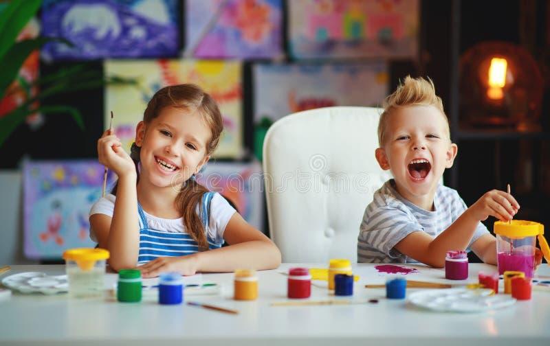 I bambini divertenti ragazza e ragazzo disegna la risata con la pittura immagini stock