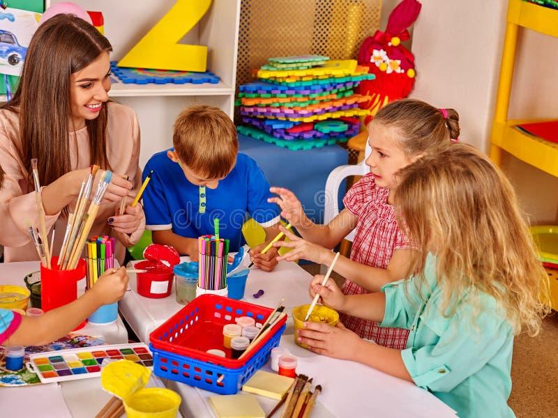I bambini e l'insegnante sono impegnati nelle attività creative di istruzione fotografie stock