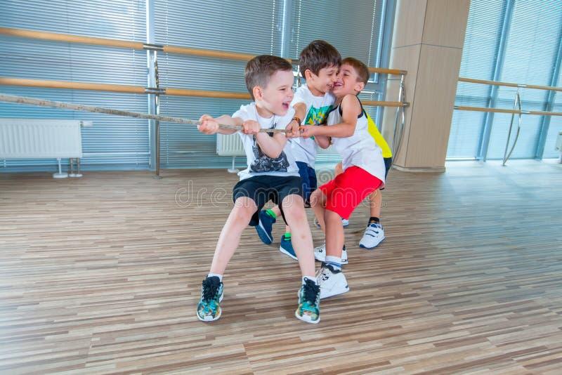 I bambini e la ricreazione, gruppo di scuola multietnica felice scherza il gioco del conflitto con la corda in palestra immagine stock libera da diritti