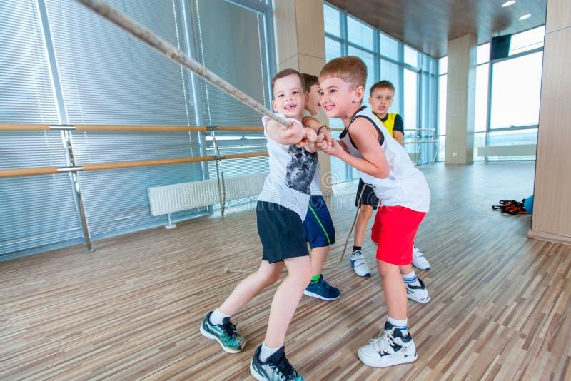 I bambini e la ricreazione, gruppo di scuola multietnica felice scherza il gioco del conflitto con la corda in palestra fotografia stock libera da diritti