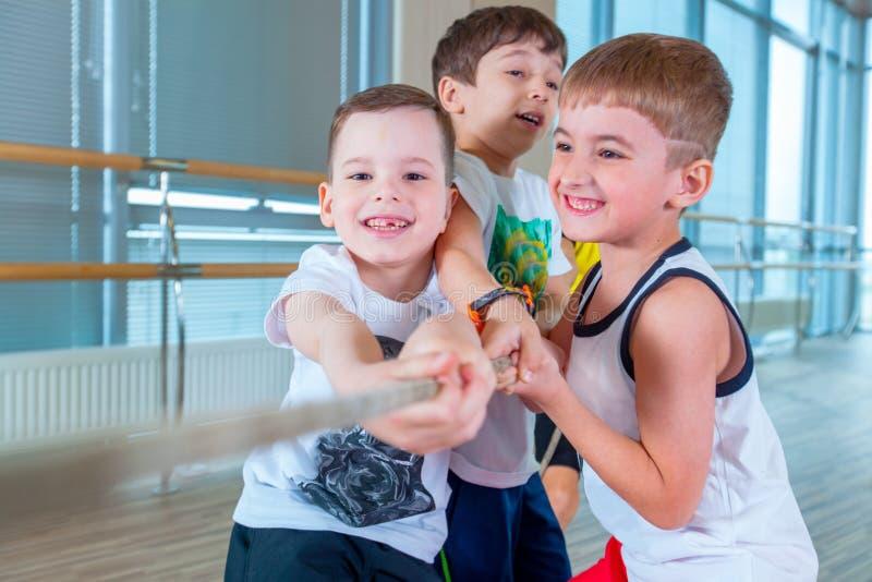 I bambini e la ricreazione, gruppo di scuola multietnica felice scherza il gioco del conflitto con la corda in palestra immagini stock