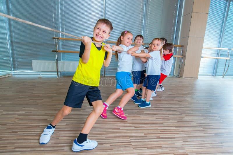 I bambini e la ricreazione, gruppo di scuola multietnica felice scherza il gioco del conflitto con la corda in palestra fotografie stock