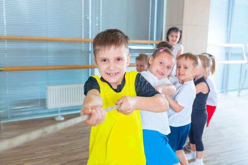 I bambini e la ricreazione, gruppo di scuola multietnica felice scherza il gioco del conflitto con la corda in palestra immagine stock