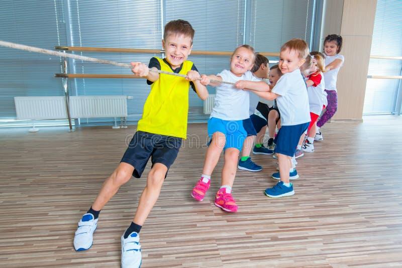 I bambini e la ricreazione, gruppo di scuola multietnica felice scherza il gioco del conflitto con la corda in palestra fotografia stock