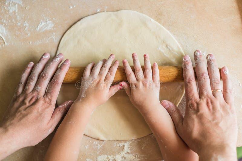 I bambini e le mani del papà hanno rotolato la pasta immagine stock libera da diritti