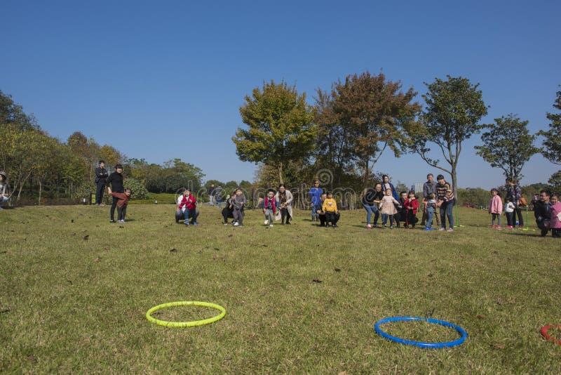 I bambini ed i genitori di asilo stanno partecipando ad un'attività del genitore-bambino al parco della montagna del longback pro fotografia stock libera da diritti