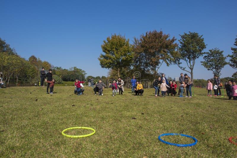 I bambini ed i genitori di asilo stanno partecipando ad un'attività del genitore-bambino al parco della montagna del longback pro immagine stock