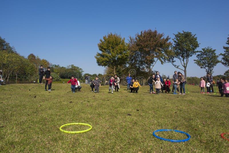 I bambini ed i genitori di asilo stanno partecipando ad un'attività del genitore-bambino al parco della montagna del longback pro immagini stock