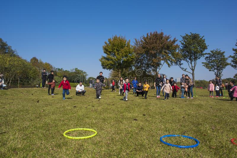 I bambini ed i genitori di asilo stanno partecipando ad un'attività del genitore-bambino al parco della montagna del longback pro fotografia stock