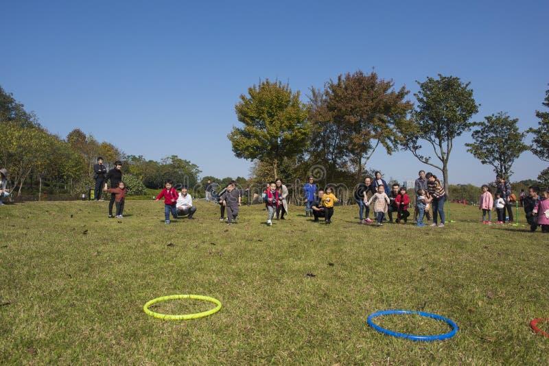 I bambini ed i genitori di asilo stanno partecipando ad un'attività del genitore-bambino al parco della montagna del longback pro fotografie stock libere da diritti