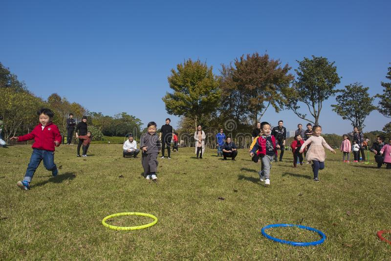 I bambini ed i genitori di asilo stanno partecipando ad un'attività del genitore-bambino al parco della montagna del longback pro fotografie stock