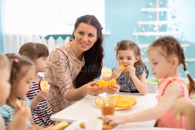 I bambini ed il personale sanitario mangiano insieme la frutta come spuntino nell'asilo, nella scuola materna o nella guardia immagini stock libere da diritti