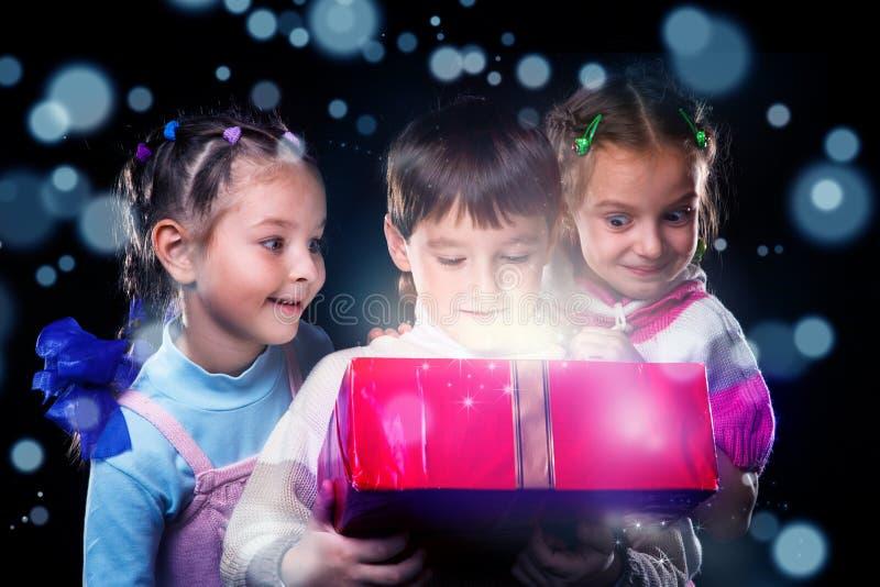 I bambini felici aprono una scatola attuale magica fotografia stock libera da diritti