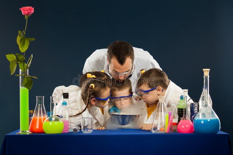 I bambini felici con lo scienziato che fa la scienza sperimenta in laboratorio immagini stock libere da diritti