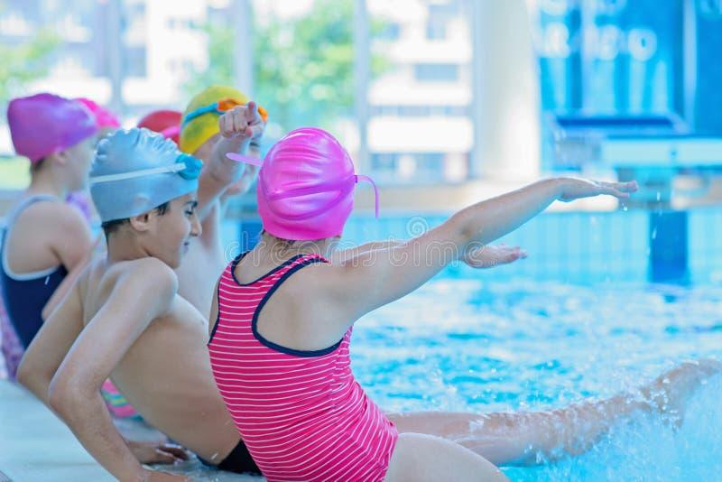 I bambini felici scherza il gruppo alla classe della piscina che impara nuotare fotografia stock