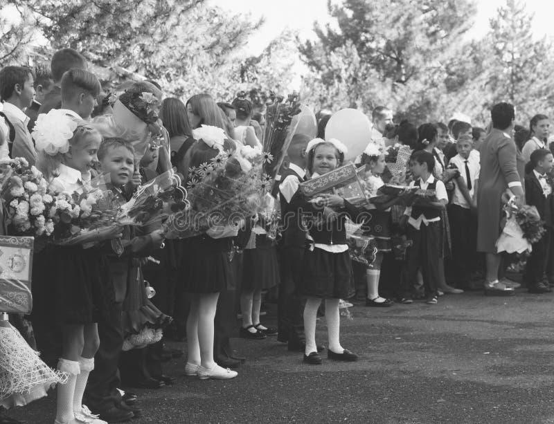 I bambini felici si sono iscritti alla prima classe con i regali in loro mani sulla linea solenne del ` s della scuola nel giorno fotografie stock