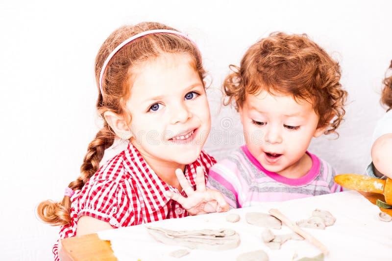 I bambini felici sono impegnati con argilla da modellare immagine stock