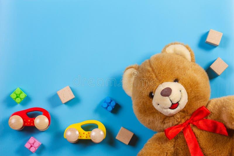 I bambini gioca il fondo con l'orsacchiotto, le automobili di legno, i blocchetti della costruzione ed i cubi fotografie stock libere da diritti