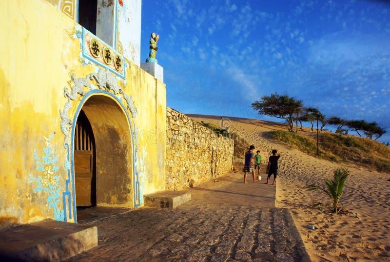 I bambini giocano a calcio al portone del tempio accanto alla collina della sabbia. TUY PHONG, VIETNAM 3 FEBBRAIO immagine stock libera da diritti