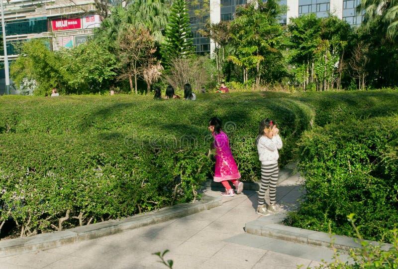 I bambini giocano a nascondino in un parco verde della città fotografie stock