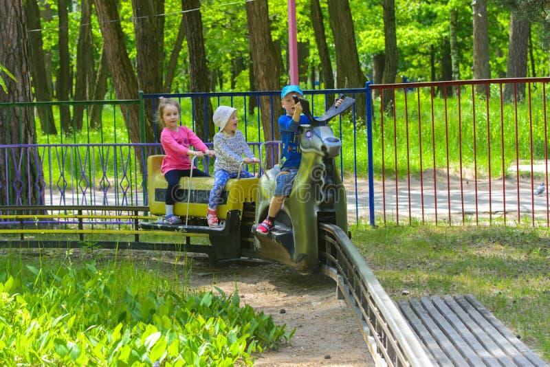 I bambini guidano sul carosello sul campo da gioco per bambini fotografia stock libera da diritti