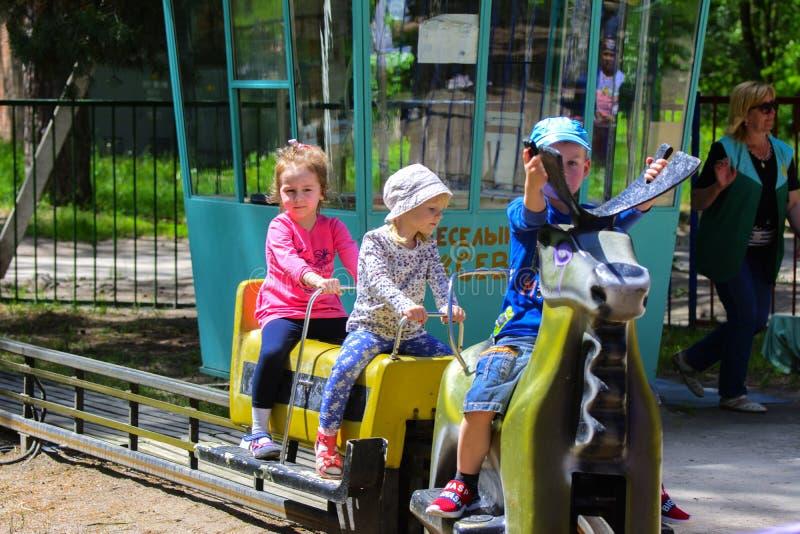 I bambini guidano sul carosello sul campo da gioco per bambini immagine stock libera da diritti