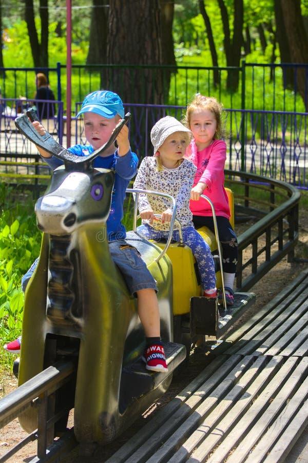 I bambini guidano sul carosello sul campo da gioco per bambini immagine stock