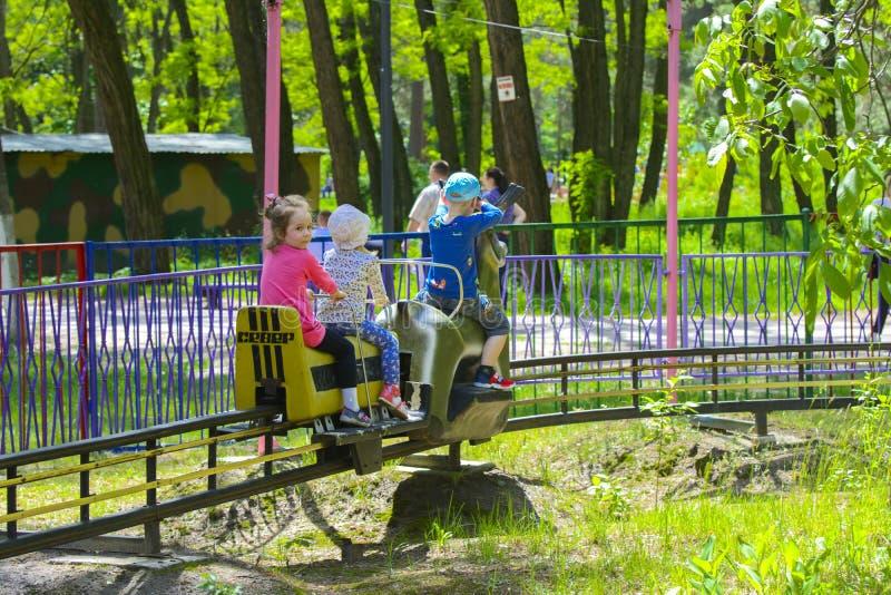 I bambini guidano sul carosello sul campo da gioco per bambini immagini stock