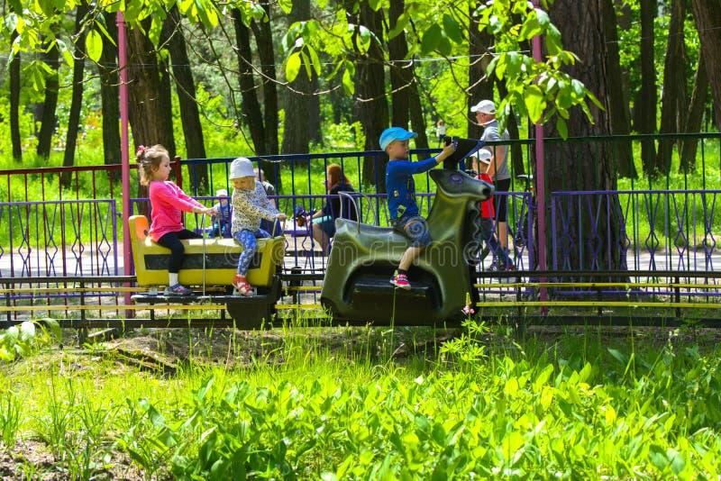 I bambini guidano sul carosello sul campo da gioco per bambini immagini stock libere da diritti