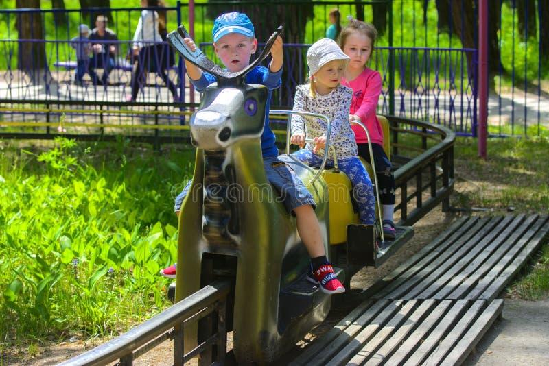I bambini guidano sul carosello sul campo da gioco per bambini fotografie stock