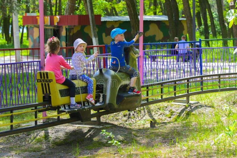 I bambini guidano sul carosello sul campo da gioco per bambini fotografia stock