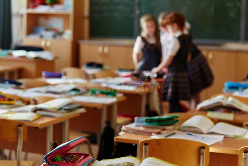 I bambini hanno lasciato le loro cartelle e taccuini sulle tavole e sono andato mettere Tre piccoli studenti restati nella classe fotografia stock