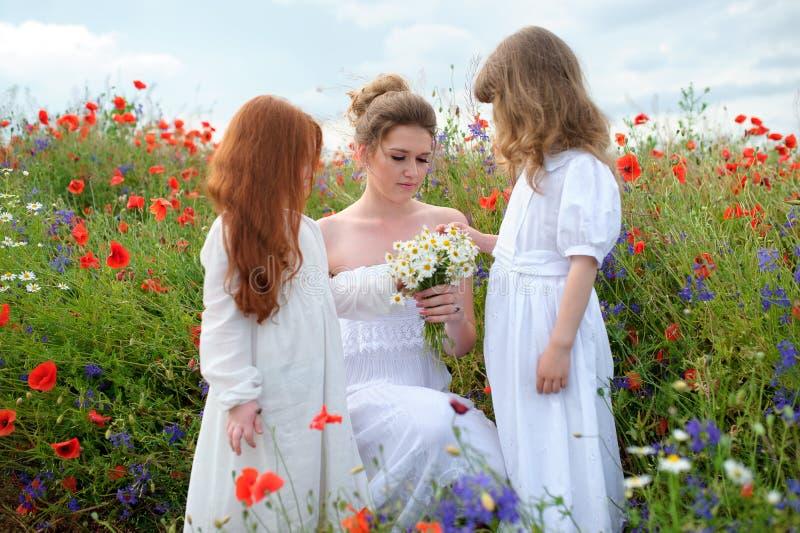 I bambini hanno portato i fiori selvaggi raccolti per la mamma Ou felice della famiglia fotografia stock