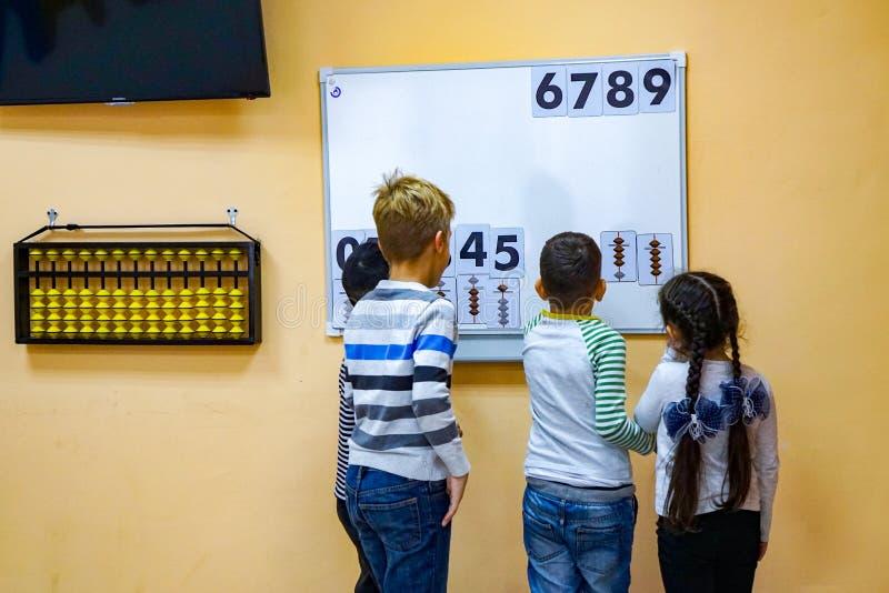 I bambini imparano il per la matematica, numeri su una lavagna immagine stock