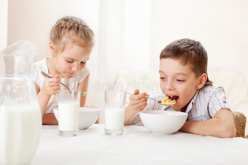 I bambini mangiano la prima colazione fotografia stock libera da diritti