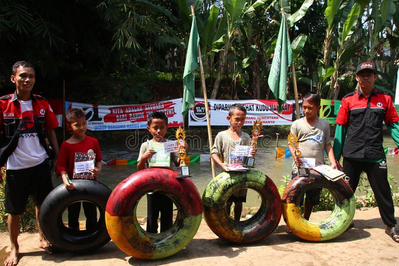 I bambini nel villaggio giocano gli acquascivoli allegri sul fiume, immagine stock libera da diritti