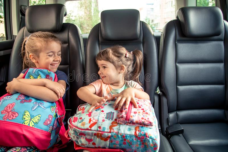 I bambini nell'automobile vanno a scuola, fronti felici e dolci delle sorelle fotografie stock
