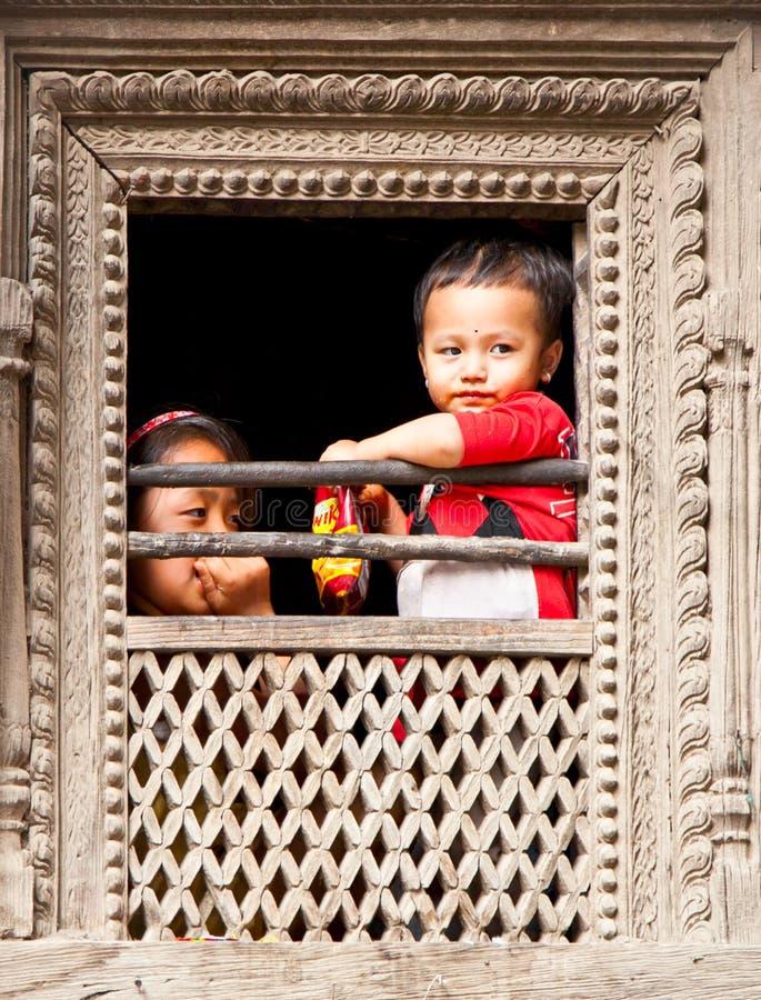 I bambini nepalesi guardano dalla finestra in Bhaktapur, Nepal. fotografia stock libera da diritti